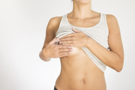 breast examination: Close up view of the female torso with a grey shirt testing her breast for cancer flattening the tissue with one hand and manipulating to detect lumps with the fingers on her other hand