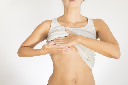 bare breasts: Close up view of the female torso with a grey shirt testing her breast for cancer flattening the tissue with one hand and manipulating to detect lumps with the fingers on her other hand