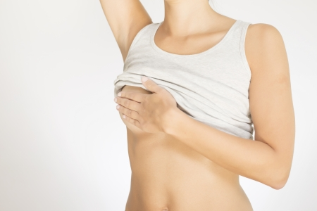 naked woman breasts: Close up view of the female torso with a grey shirt testing her breast for cancer flattening the tissue with one hand and manipulating to detect lumps with the fingers on her other hand