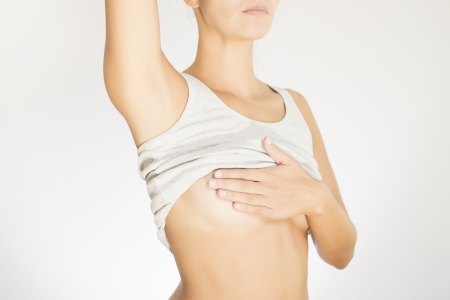 Close up view of the female torso with a grey shirt testing her breast for cancer flattening the tissue with one hand and manipulating to detect lumps with the fingers on her other hand photo