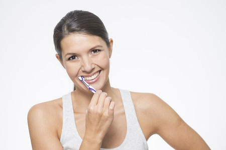 tooth decay: Attractive woman practising dental hygiene brushing her teeth with a toothbrush and toothpaste to prevent tooth decay or caries , isolated on white Stock Photo