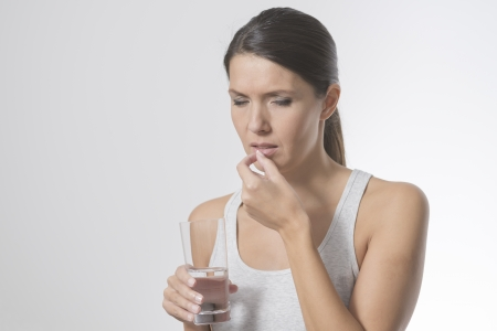 Attractive woman taking medication holding a glass of water in one hand as she slips a tablet or antibiotic into her mouth to treat an illness, or a painkiller or supplement photo