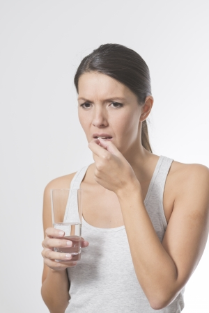 taking pill: Attractive woman taking medication holding a glass of water in one hand as she slips a tablet or antibiotic into her mouth to treat an illness, or a painkiller or supplement Stock Photo