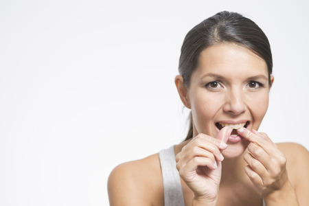 flossing: Woman flossing her teeth with dental floss to remove any food particles or bacteria caught between her teeth to prevent tooth decay or caries