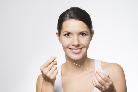 Woman flossing her teeth with dental floss to remove any food particles or bacteria caught between her teeth to prevent tooth decay or caries photo