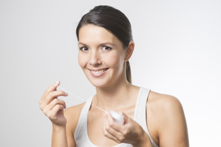 tooth decay: Woman flossing her teeth with dental floss to remove any food particles or bacteria caught between her teeth to prevent tooth decay or caries