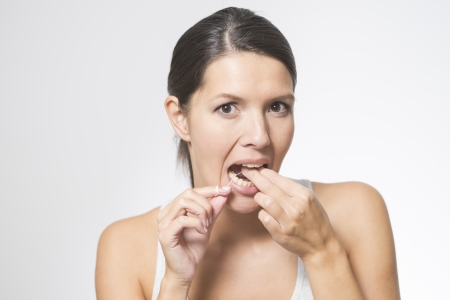 floss: Woman flossing her teeth with dental floss to remove any food particles or bacteria caught between her teeth to prevent tooth decay or caries