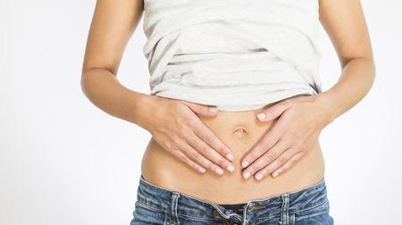Vrouw met haar maandelijkse menstruatiepijn klemde haar buik met haar handen als ze wordt benadrukt door de aanhoudende krampen, torso van haar handen en buik geïsoleerd op wit