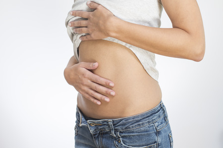 sufferer: Woman with her monthly menstrual pains clutching her stomach with her hands as she becomes stressed by the ongoing cramps, torso view of her hands and tummy isolated on white