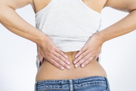 Rückansicht einer Frau mit Schmerzen im unteren Rücken halten ihre Hände auf dem Rücken und der Wirbelsäule, um den Schmerz in ihren Muskeln oder der Wirbelsäule Wirbel und Bandscheiben durch Stress, Verletzungen oder Krankheit gebracht entlasten