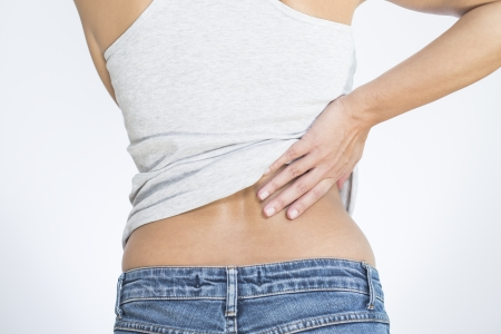 throbbing: Rear view of a woman with lower back pain clutching her hands to her back and spine to relieve the ache in her muscles or spinal vertebrae and discs brought on by stress, injury or disease