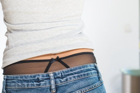 expose: View from behind of a shapely woman in jeans wearing black panties which are visible where her t-shirt has creased and rucked up her back to expose her midriff Stock Photo