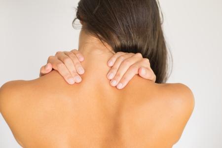 Frau mit oberen Rücken-und Nackenschmerzen nackt mit dem Rücken zur Kamera und ihre Hand reiben ihre Schultermuskulatur in der Nähe der Wirbelsäule Standard-Bild