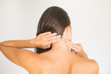 Woman with upper back and neck pain standing naked with her back to the camera and her hand rubbing her shoulder muscles close to the spine photo