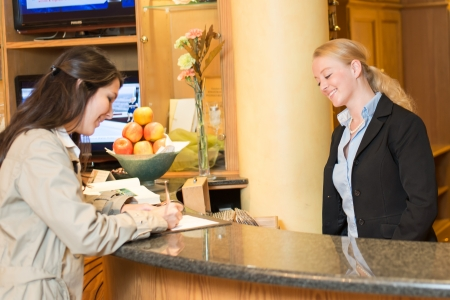 Young woman checking in at the hotel reception with friendly receptionist photo