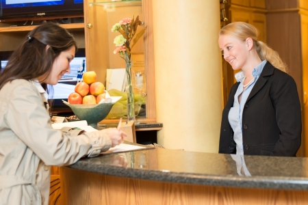 checking in: Young woman checking in at the hotel reception with friendly receptionist