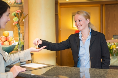 Smiling friendly hotel receptionist standing behind the service desk in a hotel lobby booking in a female client handing her the room keys for her stay during her vacation photo