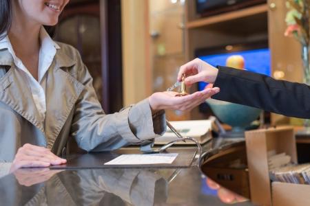 vrouwelijke gast wordt overhandigd de sleutels van hotelkamer door receptioniste, reizen en toerisme-concept