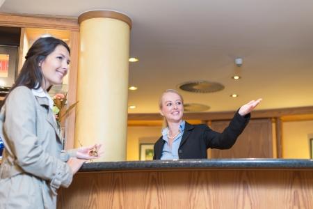 hospedaje: �ngulo de visi�n baja de una hermosa agradable sonriente recepcionista detr�s del mostrador de servicio en un vest�bulo del hotel ayuda a una hu�sped femenina atractiva se�alando con la mano el camino a su alojamiento