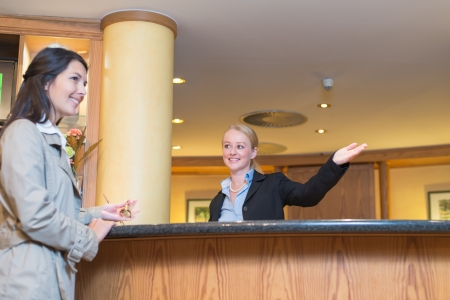 Low angle view of a beautiful friendly smiling receptionist behind the service desk in a hotel lobby helping an attractive female guest indicating with her hand the way to her accomodation photo