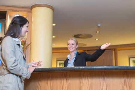 그녀의 손으로 그녀의 숙박에 방법을 나타내는 매력적인 여성 손님을 돕는 호텔 로비에서 서비스 데스크 뒤에 아름 다운 친절 웃는 접수의 낮은 각도