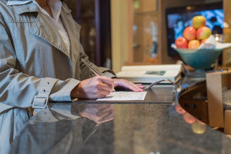 checking in: female hotel guest filling in registration form upon checking in, service and tourism concept Stock Photo