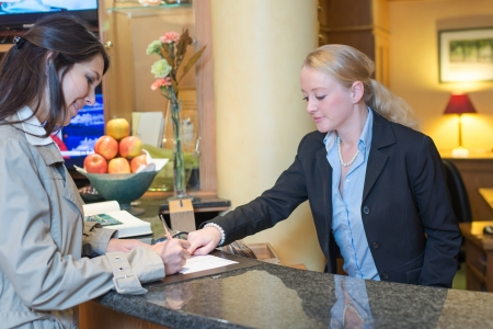 hospitality: Smiling attractive young receptionist helping a hotel guest check in pointing to information on the form that needs to be completed as they stand at the service desk in the lobby