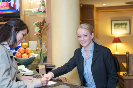 formalities: Smiling attractive young receptionist helping a hotel guest check in pointing to information on the form that needs to be completed as they stand at the service desk in the lobby