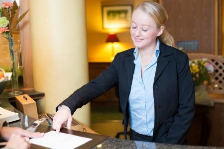 Sonriendo atractiva joven recepcionista ayudar a una cuenta de cliente en el hotel, que apunta a la información en el formulario que debe ser completado en su forma actual en el mostrador de servicio en el vestíbulo