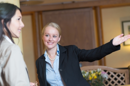 Beautiful friendly smiling receptionist behind the service desk in a hotel lobby helping an attractive female guest indicating with her hand the way to her accomodation