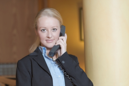 Beautiful blond woman wearing a suit answering an office telephone at work photo