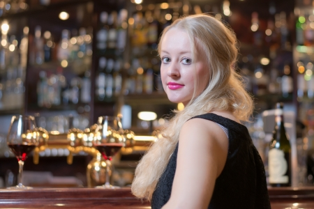 formal party: Beautiful young blond woman seated at a bar counter in an upmarket in a hotel, club or restaurant looking back over her shoulder at the camera