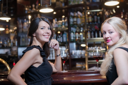 Two beautiful elegant young women drinking at an upmarket hotel or nightclub sitting at the bar counter turning to look at the camera with lovely friendly smiles photo