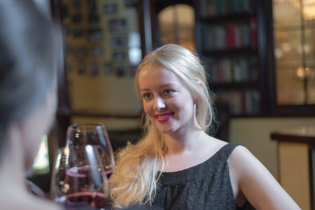 cocktaildress: Beautiful smiling young blond woman in a black cocktail dress enjoying a night out with a female friend in a hotel or club drinking a glass of red wine