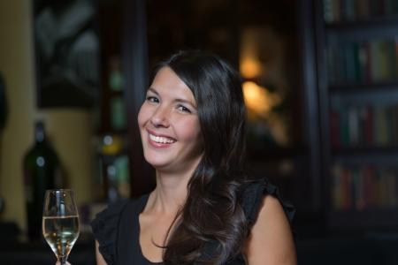 cocktaildress: Mooie stijlvolle gelukkige jonge vrouw met een charmante glimlach het dragen van een zwarte cocktail jurk vieren 's nachts met een glas champagne in haar hand