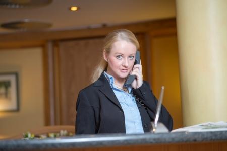 llamando: Hermosa mujer rubia que llevaba un traje de contestar un teléfono de oficina en el trabajo Foto de archivo