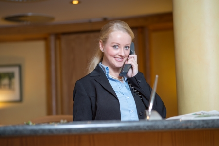 answering call: Beautiful blond woman wearing a suit answering an office telephone at work