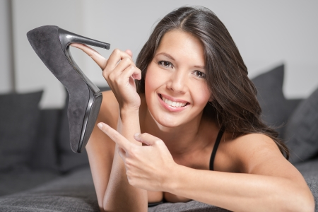 Attractive young woman holding up an elegant high heeled black ladies court shoe in a plush finish, close up of her face and the shoe photo