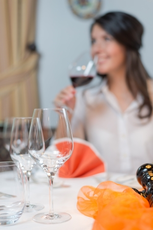Attractive young brunette woman drinking a glass of red wine and looking away to the left of the camera photo