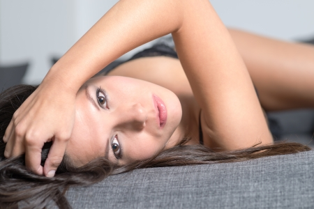 tantalising: Beautiful appealing young woman lying on her back in seductive lingerie looking back at the camera with a serious wide eyed expressiong