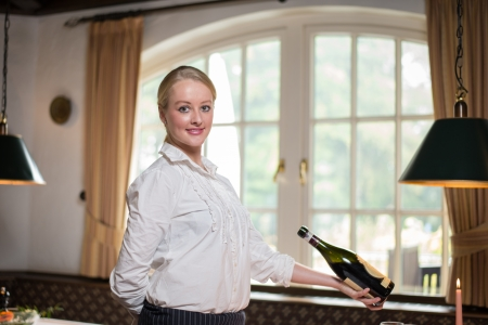 Young blond waitress in restaurant holding a bottle of red wine photo