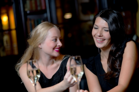 Two beautiful young women enjoying a glass of wine on a night out using their mobile phones laughing at the conversation and text message photo