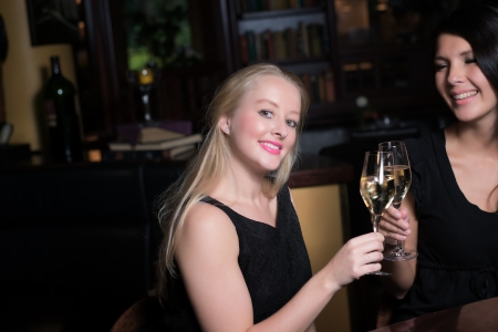 chilled out: Two beautiful elegant women friends in stylish simple black cocktail dresses toasting each other with glasses of chilled white wine as they celebrate on a night out together