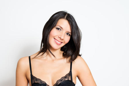 lacy: Beautiful young brunette woman with a lovely smile wearing sexy lacy black lingerie, head and shoulders studio portrait on white with copyspace