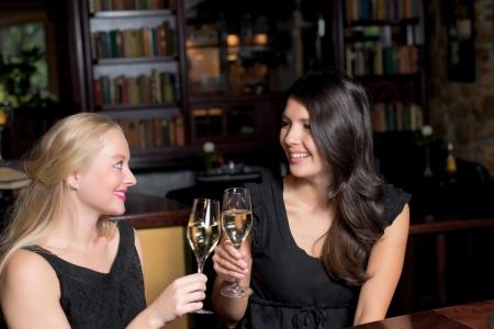 mujeres elegantes: Dos hermosas mujeres elegantes amigos en simples elegantes vestidos de c�ctel negro brindando con copas de champagne en la celebraci�n de una noche juntos Foto de archivo