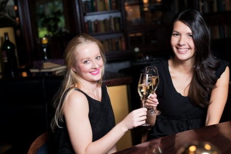 chilled out: Two beautiful elegant women friends in stylish simple black cocktail dresses toasting each other with glasses of chilled champagne as they celebrate on a night out together Stock Photo