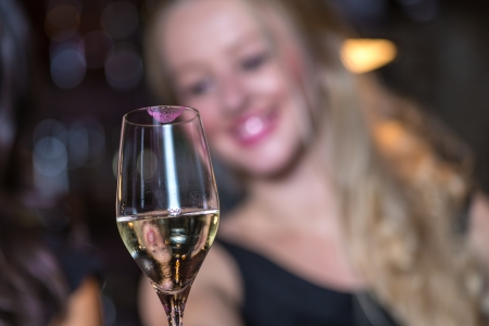 Happy smiling women celebrating with champagne in a restaurant or nightclub while out partying with focus to the elegant glass of champagne in the foreground photo