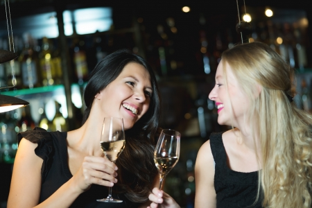 Two happy female good friends, one blonde and one brunette, toasting with champagne or white wine in a trendy nightclub