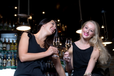Two beautiful young women wearing elegant black dresses, celebrating with alcoholic drinks in a fancy location photo