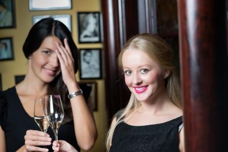 mujeres elegantes: Dos hermosas mujeres elegantes amigos en elegantes simples vestidos de c�ctel negro de beber un vaso de champa�a fr�a en la celebraci�n de una noche juntos